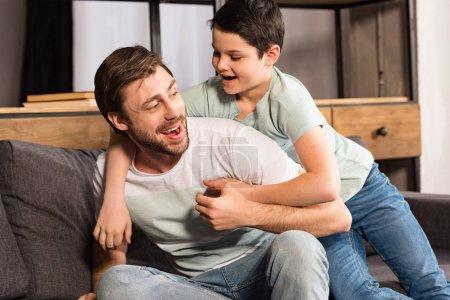 Photo pour Fils riant et papa s'asseyant sur le sofa et ayant l'amusement dans le salon - image libre de droit