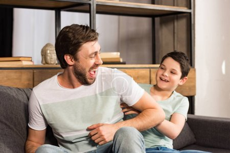 Photo for Laughing son and dad sitting on sofa and having fun in living room - Royalty Free Image