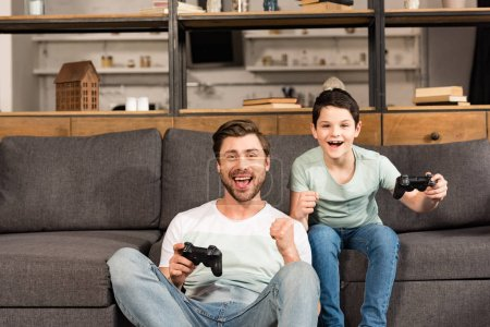 Photo for KYIV, UKRAINE - APRIL 17, 2019: smiling father and son holding gamepads and playing video games in living room - Royalty Free Image