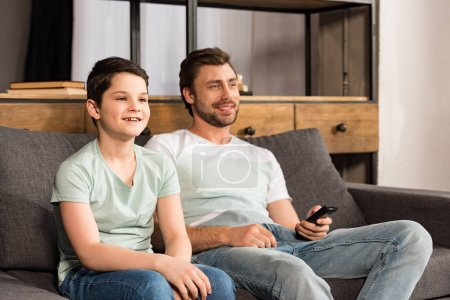 Photo pour Fils et père souriants avec le contrôleur à distance observant la tv dans le salon - image libre de droit