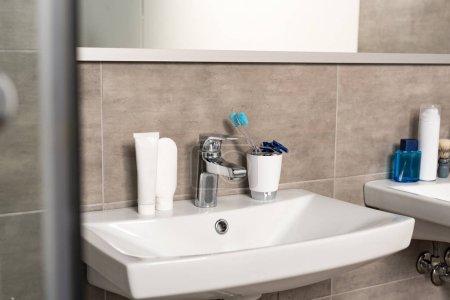 Photo pour Brosses à dents, dentifrice et rasoirs sur évier dans la salle de bain - image libre de droit