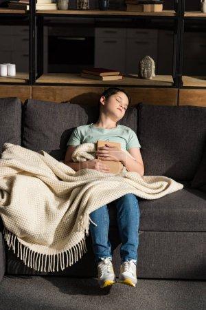 Photo pour Garçon avec le livre dormant sous la couverture dans le salon - image libre de droit