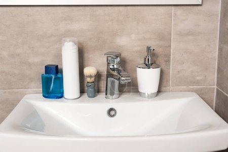 Photo pour Lotion, mousse à raser, savon liquide et brosse sur évier dans la salle de bain - image libre de droit