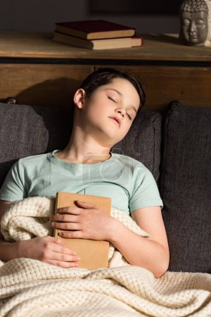 Photo for Boy with book sleeping under blanket in living room - Royalty Free Image