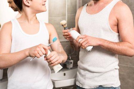 Photo pour Vue recadrée de fils brossant les dents et papa se rasant le matin dans la salle de bain - image libre de droit