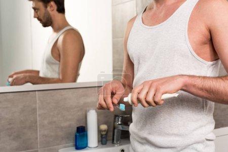 Photo pour Vue recadrée de l'homme appliquant le dentifrice sur la brosse à dents le matin dans la salle de bains - image libre de droit