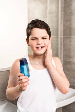 Photo pour Garçon préadolescent insatisfait appliquant la lotion sur le visage et regardant l'appareil-photo dans la salle de bains - image libre de droit
