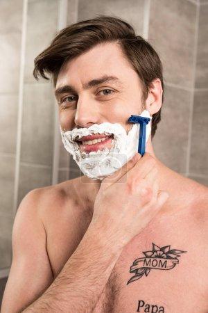 Photo pour Barbe de rasage d'homme de sourire avec le rasoir dans la salle de bains - image libre de droit