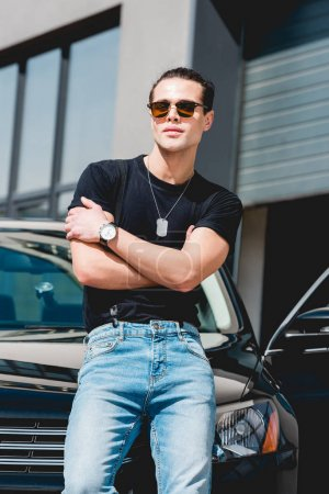 Photo for Handsome stylish man in sunglasses posing near car with crossed arms - Royalty Free Image