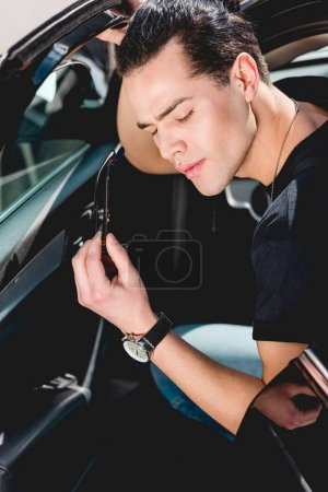 Photo for Handsome stylish man holding sunglasses and posing while sitting in car - Royalty Free Image