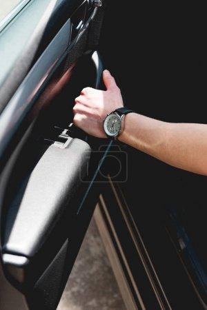Photo pour Vue cultivée de l'homme avec la montre s'asseyant dans la voiture et manipulant la poignée de porte - image libre de droit