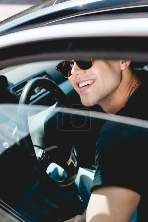 Photo for Selective focus of handsome stylish man in sunglasses smiling and sitting in car - Royalty Free Image