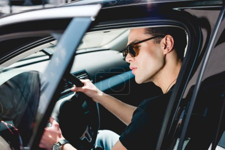 Photo for Selective focus of handsome stylish man in sunglasses driving car - Royalty Free Image