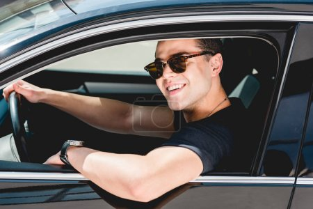 Photo for Handsome stylish man in sunglasses smiling and sitting in car - Royalty Free Image