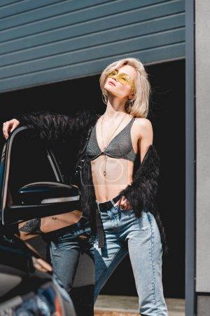 Photo pour Belle jeune femme à la mode dans des glaces posant près de la voiture et du garage - image libre de droit