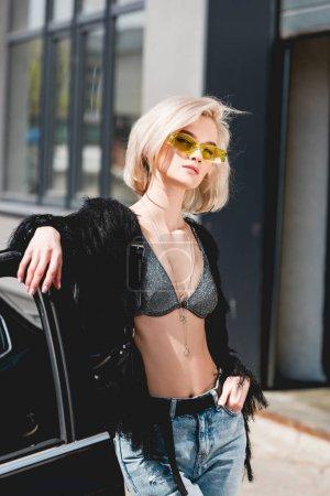 Photo pour Belle jeune femme à la mode dans des glaces posant près de la voiture - image libre de droit