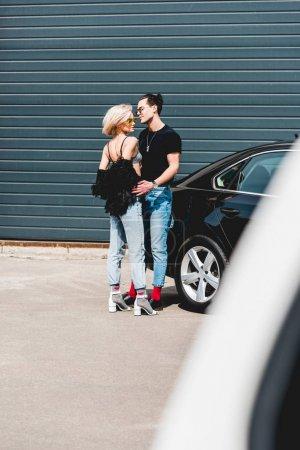 Photo pour Homme beau à la mode et belle fille posant près de la voiture - image libre de droit