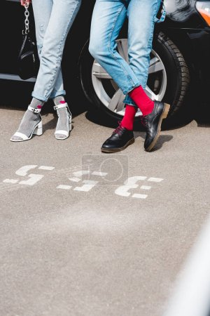 Photo for Cropped view of stylish man and girl in denim posing near car - Royalty Free Image