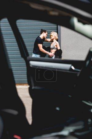 Photo pour Foyer sélectif de l'homme élégant et de la belle fille posant près de la porte de garage - image libre de droit