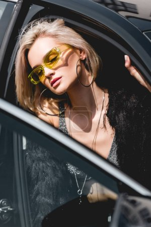 Photo for Beautiful fashionable sexy young woman in glasses posing in car with eyes closed - Royalty Free Image