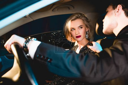 Photo for Stylish man and beautiful sensual young woman in formal wear sitting in car - Royalty Free Image