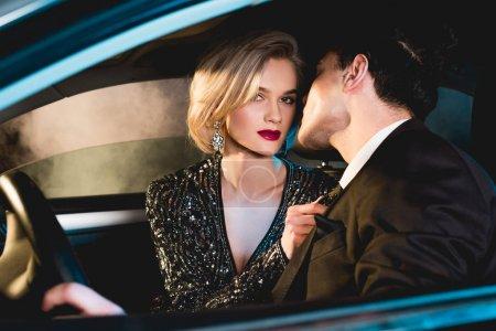 Photo pour Homme élégant et belle jeune femme à la mode en tenue formelle assis dans la voiture - image libre de droit