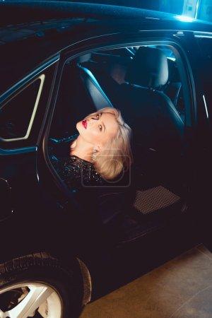 Photo pour Belle jeune femme à la mode regardant l'appareil-photo tout en posant dans la voiture - image libre de droit
