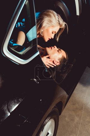 Photo for Handsome man and attractive young woman embracing in car - Royalty Free Image