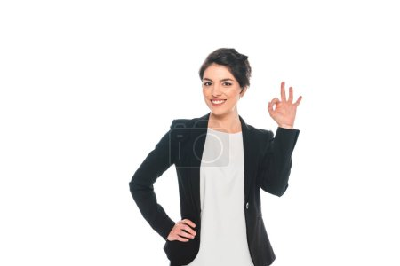 Photo for Cheerful mixed race businesswoman showing ok gesture isolated on white - Royalty Free Image