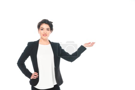 Foto de Attractive mixed race businesswoman holding hand on hip and gesturing while smiling at camera isolated on white - Imagen libre de derechos