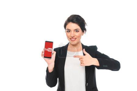 Foto de Kiev, Ucrania - 24 de abril de 2019: Atractiva empresaria de carreras mixtas señalando con el dedo en el teléfono inteligente con la aplicación de Youtube en la pantalla aislada en blanco. - Imagen libre de derechos