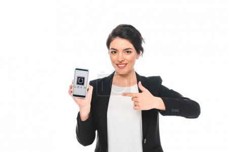 Photo pour KYIV, UKRAINE - APRIL 24, 2019: Beautiful mixed race businesswoman pointing with finger at smartphone with Uber app on screen while smiling at camera isolated on white. - image libre de droit