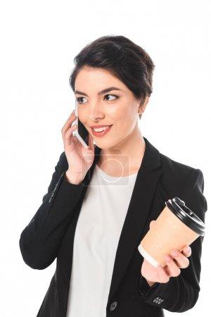 Photo for Smiling mixed race businesswoman talking on smartphone and holding disposable cup isolated on white - Royalty Free Image