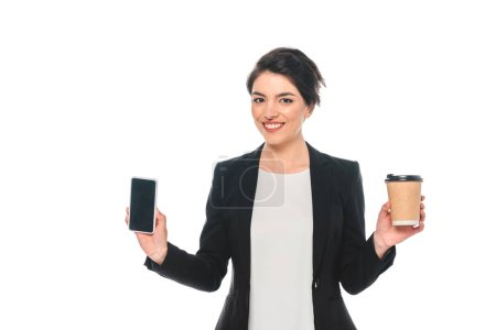 Photo for Cheerful mixed race businesswoman holding smartphone with blank screen and paper cup isolated on white - Royalty Free Image