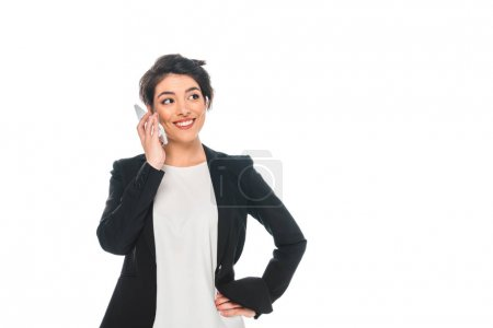 Photo pour Smiling mixed race businesswoman talking on smartphone and holding hand on hip isolated on white - image libre de droit