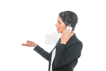 Photo for Side view of pretty mixed race businesswoman using smartphone and gesturing isolated on white - Royalty Free Image