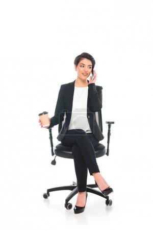 Photo pour Belle femme d'affaires de course mélangée s'asseyant dans la présidence de bureau et parlant sur le smartphone sur le fond blanc - image libre de droit
