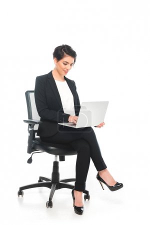 Photo pour Femme d'affaires mélangée de sourire de course s'asseyant dans la présidence de bureau et utilisant l'ordinateur portatif sur le fond blanc - image libre de droit