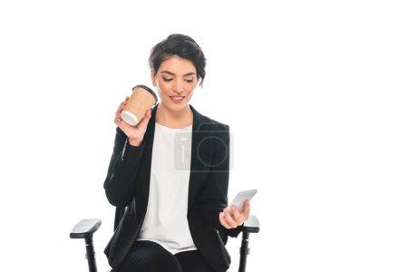 Photo pour Femme d'affaires mélangée attirante buvant le café de tasse en papier et utilisant le smartphone tout en s'asseyant dans la présidence de bureau d'isolement sur le blanc - image libre de droit