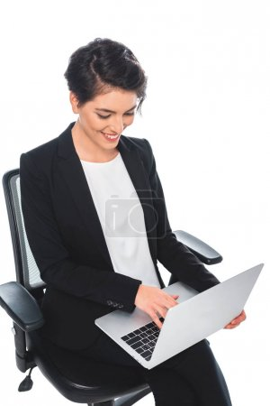 Photo pour Cheerful mixed race businesswoman using laptop while sitting in office chair isolated on white - image libre de droit