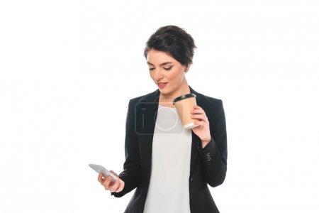 Photo pour Belle femme d'affaires de race mixte utilisant le smartphone et buvant le café de tasse jetable d'isolement sur le blanc - image libre de droit