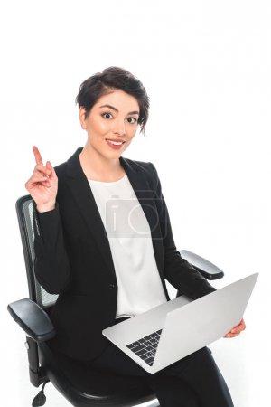 Photo pour Femme d'affaires mélangée gaie de course affichant le signe d'idée tout en s'asseyant dans la présidence de bureau et utilisant l'ordinateur portatif isolé sur le blanc - image libre de droit