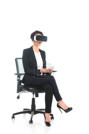 Photo pour Young mixed race businesswoman in virtual reality headset using laptop while sitting in office chair on white background - image libre de droit