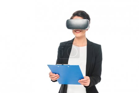 smiling mixed race businesswoman using virtual reality headset and holding clipboard isolated on white