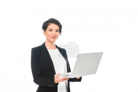 Photo for Cheerful mixed race businesswoman holding laptop and smiling at camera isolated on white - Royalty Free Image