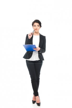 thoughtful mixed race businesswoman holding clipboard and looking away isolated on white