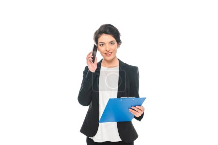 Foto de Attractive mixed race businesswoman talking on smartphone while holding clipboard and looking at camera isolated on white - Imagen libre de derechos