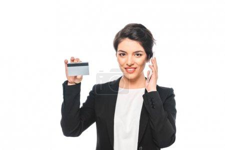 Photo pour Femme d'affaires mélangée gaie de course affichant la carte de crédit tout en parlant sur le smartphone isolé sur le blanc - image libre de droit