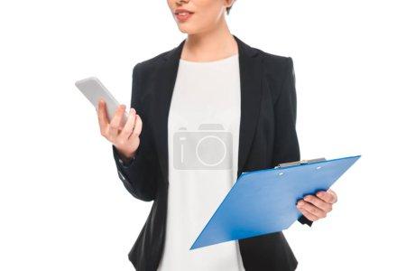 Photo pour Vue partielle de femme d'affaires de course mélangée utilisant le smartphone et retenant le presse-papiers d'isolement sur le blanc - image libre de droit
