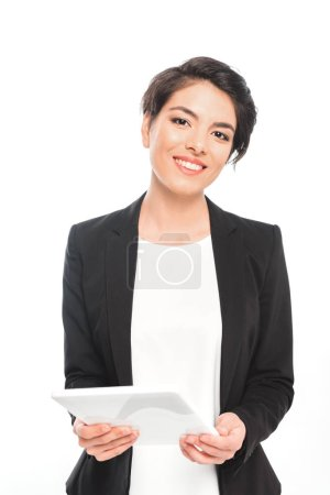 Photo pour Femme d'affaires mélangée attirante retenant la tablette numérique tout en regardant l'appareil-photo isolé sur le blanc - image libre de droit